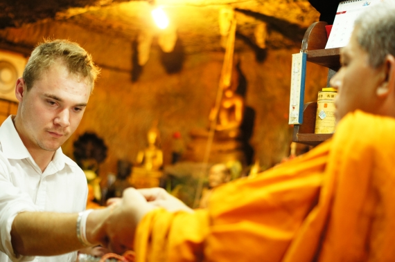 Westerners receive a blessing from a Buddhist monk in Thailand