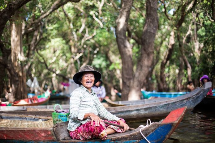 A very cheerful Cambodia womantransporting tourists through the floating village of Kompong Phluk.