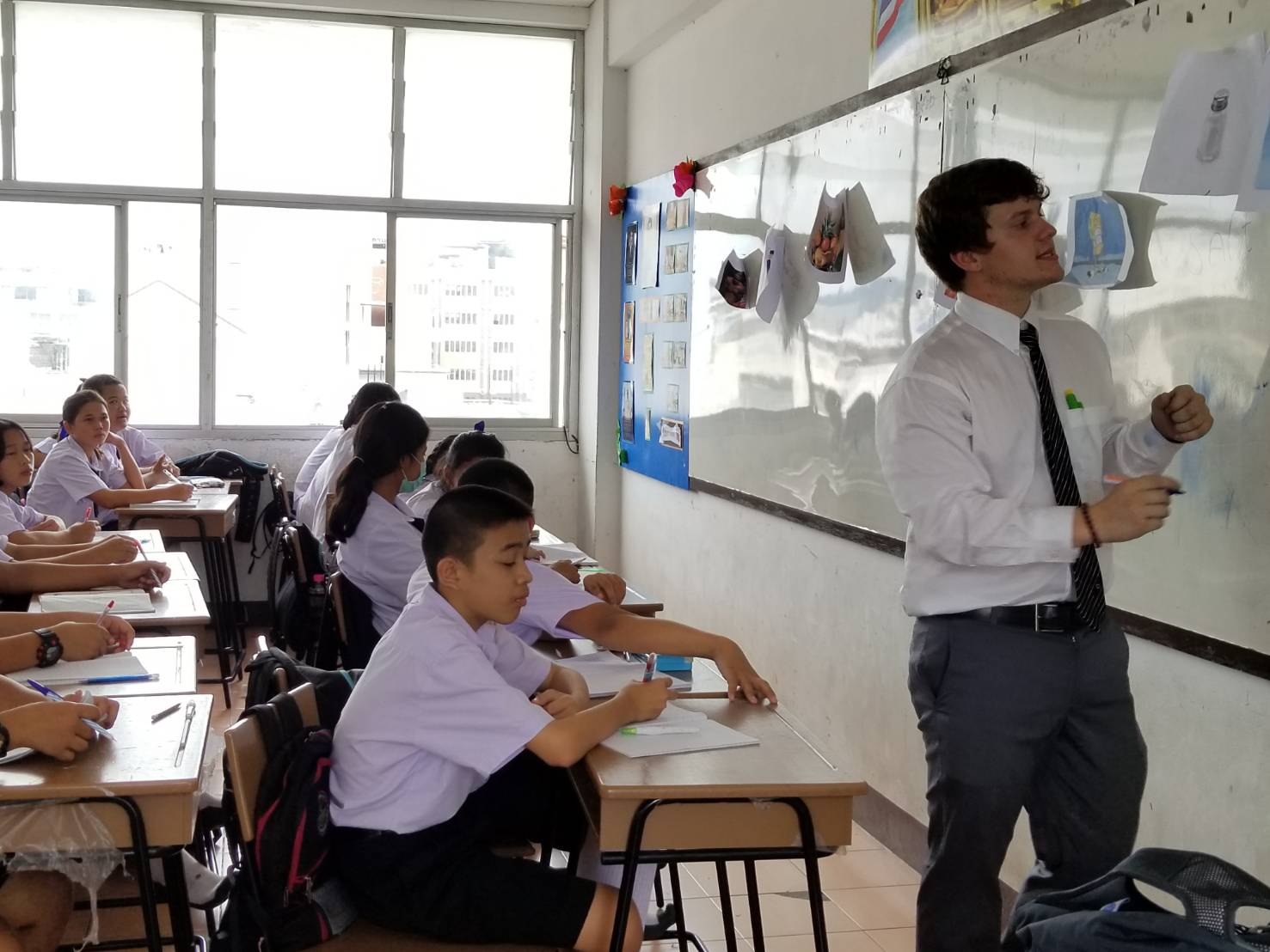 teacher writing on whiteboard in front of classroom